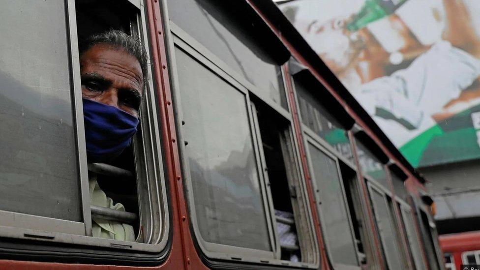 Homem de máscara com o rosto para fora da janela do ônibus olha para a câmera