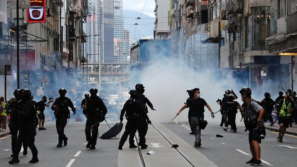 Riot police fire tear gas into the crowds to disperse anti-national security law protesters during a march at the anniversary of Hong Kong's handover to China from the UK