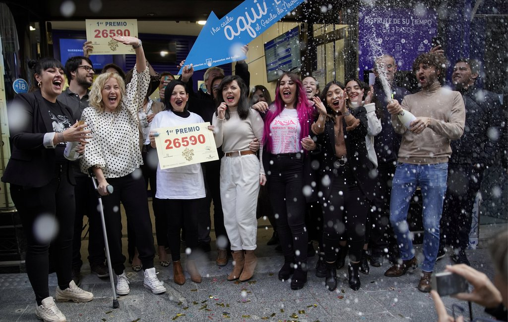 Los dueños y empelados de la tienda Doña Manolita en Madrid celebran la venta del número ganador del primer premio