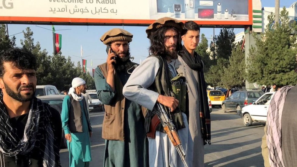 A member of Taliban (C) stands outside Hamid Karzai International Airport in Kabul, Afghanistan, August 16, 2021.