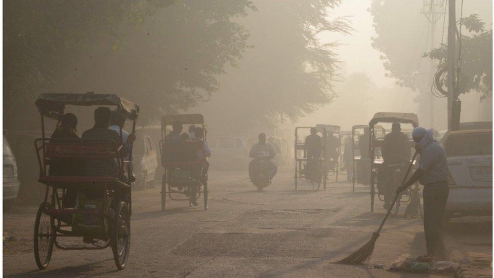 An Indian worker sweeps as smog envelops a street in the old quarter of Delhi on November 3, 2016.