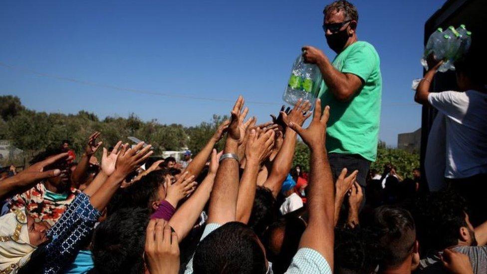 توزيع الماء والفواكه على الأشخاص الذين كانوا يتخذون من مخيم موريا ملاذاً لهم