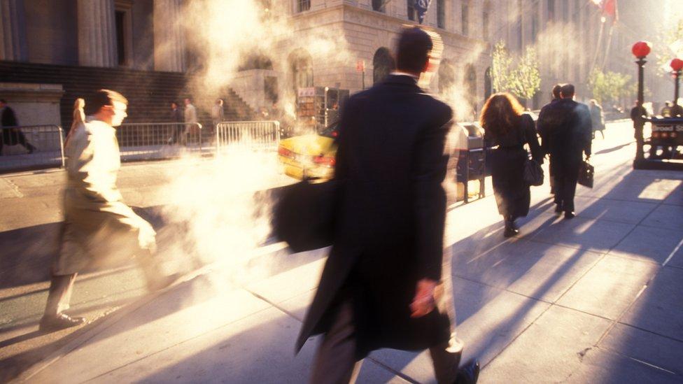 Gente caminando en Wall Street.