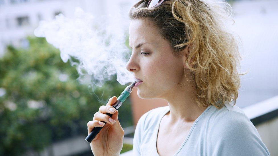 Mujer fumando un cigarrillo electrónico.