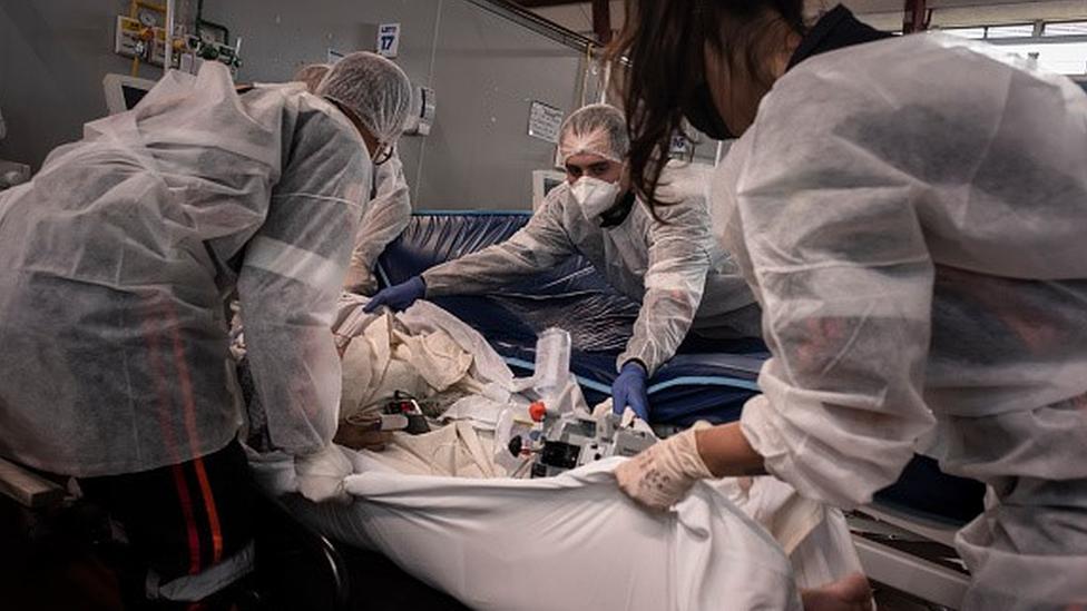 Profissionais de saúde transferem paciente de leito