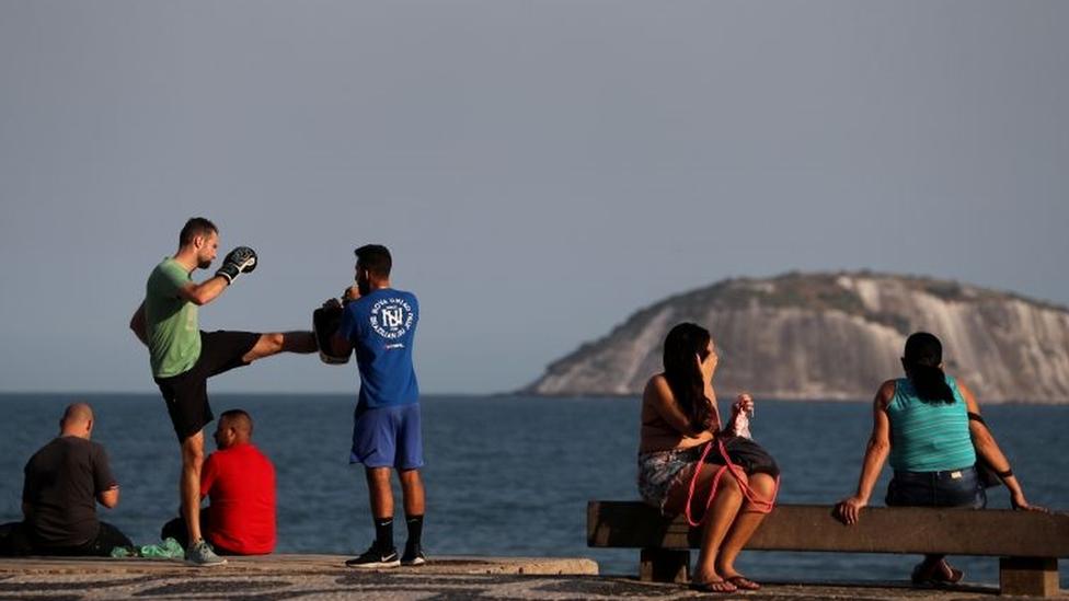 Pessoas sentadas em bancos e praticando lutas no calçadão do Rio
