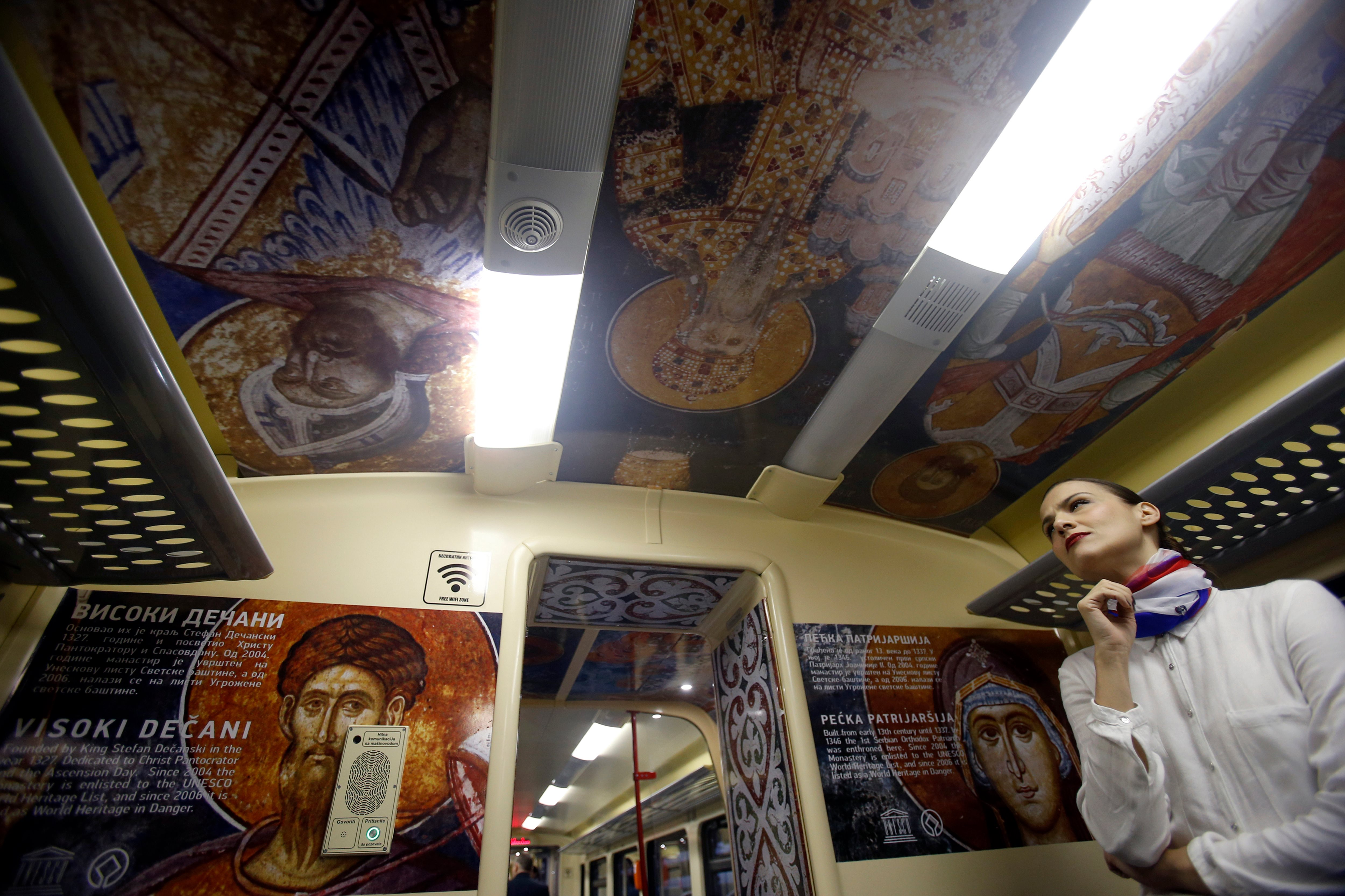 A train hostess stands in a train carriage decorated with the iconic figures as it departs from the Belgrade to Mitrovica, Kosovo at Belgrade's railway station, Serbia