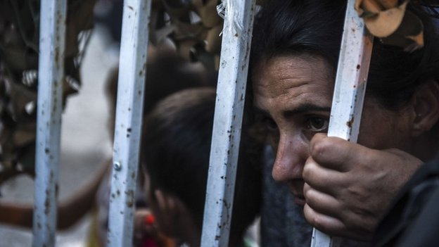 Migrants are seen behind a fence as they arrive at the refugee center in the town of Presevo, after walking from Macedonia to Serbia.