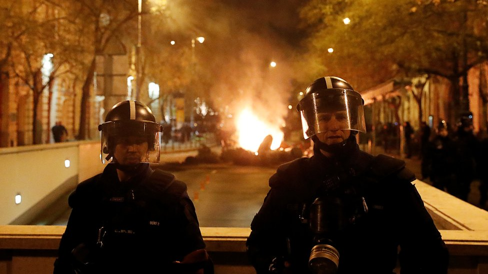 Two police in riot gear stand guard, while a fire burning in the street can be seen behind them