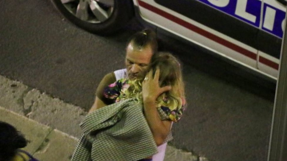 A man holds a child after a truck ploughed through Bastille Day revellers in the French resort city of Nice (15 July 2016)