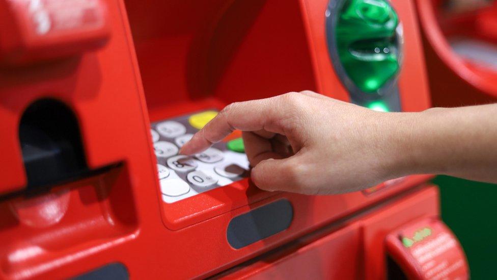 Persona sacando dinero de cajero automático