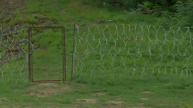 A small gate in the fence, along the Hungary-Serbia border, with no razor wire above it
