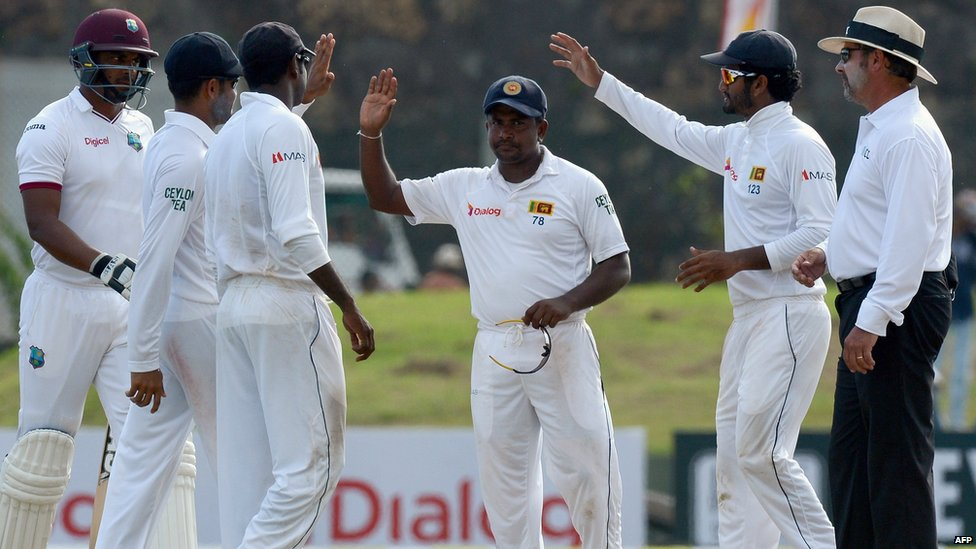 """A file picture taken on October 16, 2015 shows Sri Lankan spinner Rangana Herath (C) being congratulated by teammates at the close of play of the West Indies"""" first innings during the third day of the opening"""