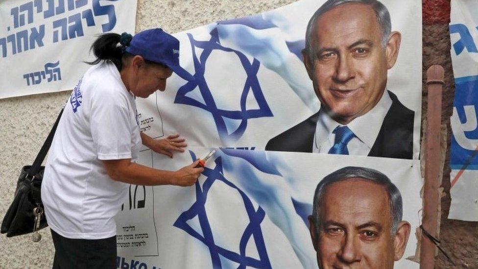 سيدة تضع ملصقات دعاية انتخابية تحمل صورة نتنياهو