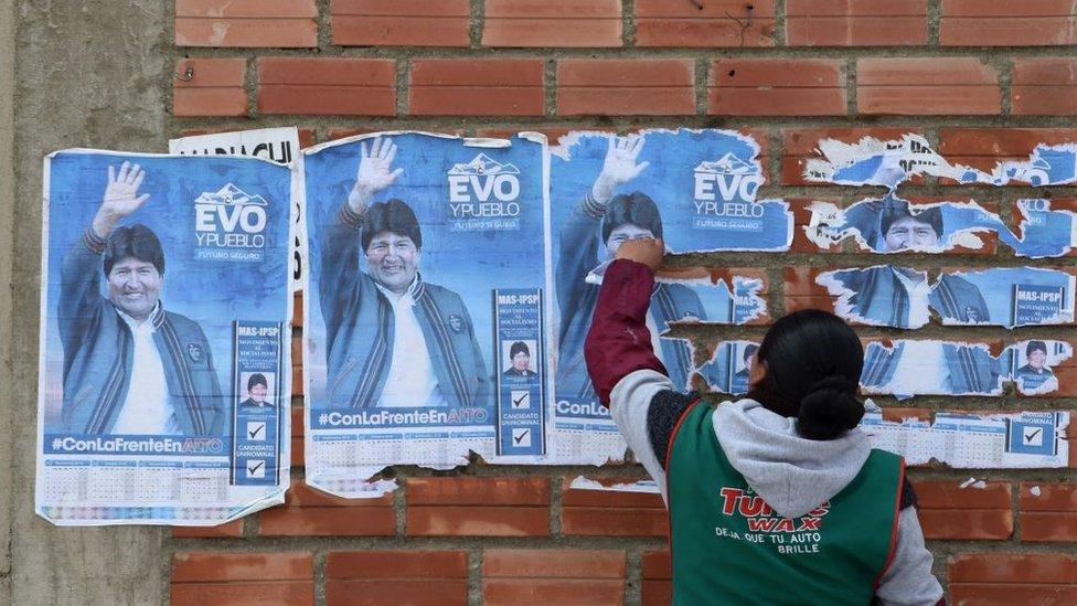 Una mujer frente a carteles de Evo MNorales