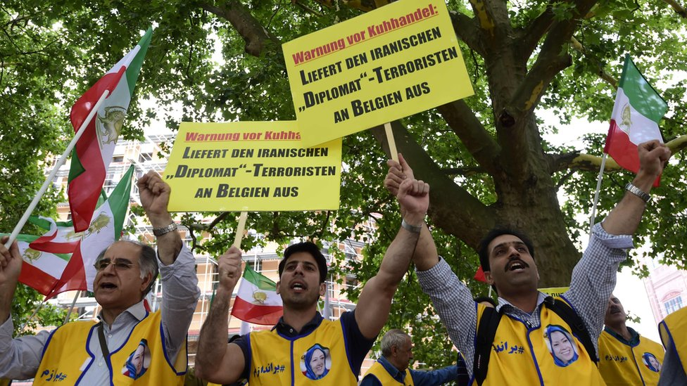 """activists of the National Council of Resistance of Iran (NCRI) hold placards reading """"Deliver the Iranian diplomat - terrorist to Belgium"""" during a demonstration calling for the extradition of a secret service officer to Belgium in front of the Federal Foreign Office in Berlin"""