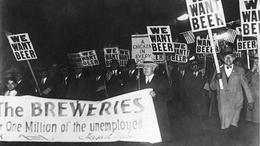 """Hombres en demostración con carteles que dicen: """"Queremos cerveza""""."""