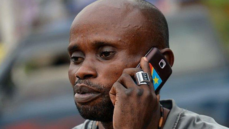 Persona usa un teléfono en Kinshasa.