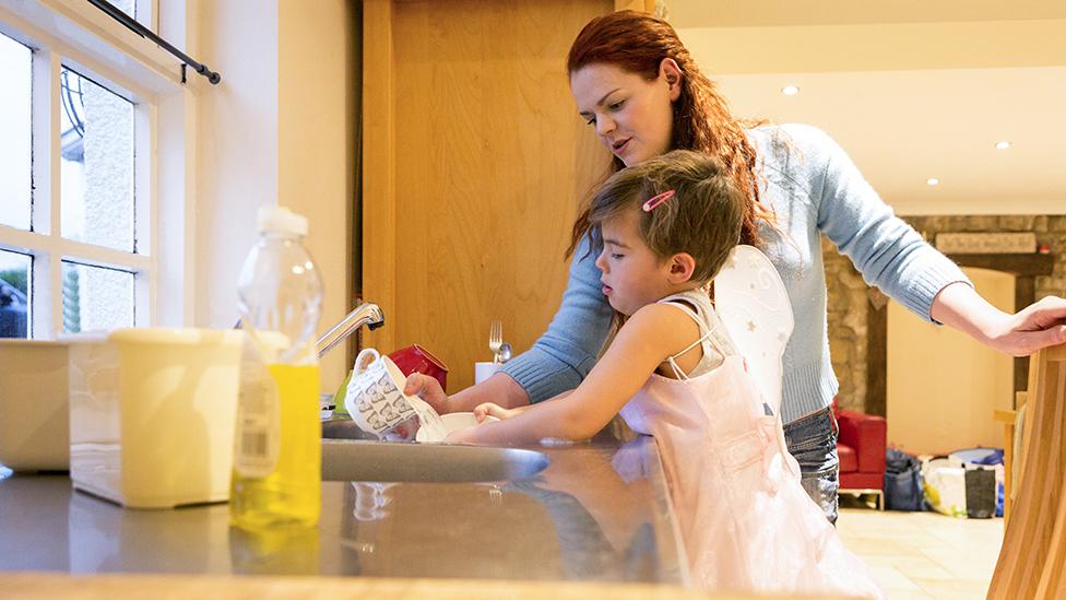 Imagen genérica de una niña trans, vestida de hada, lavando los platos con su madre.