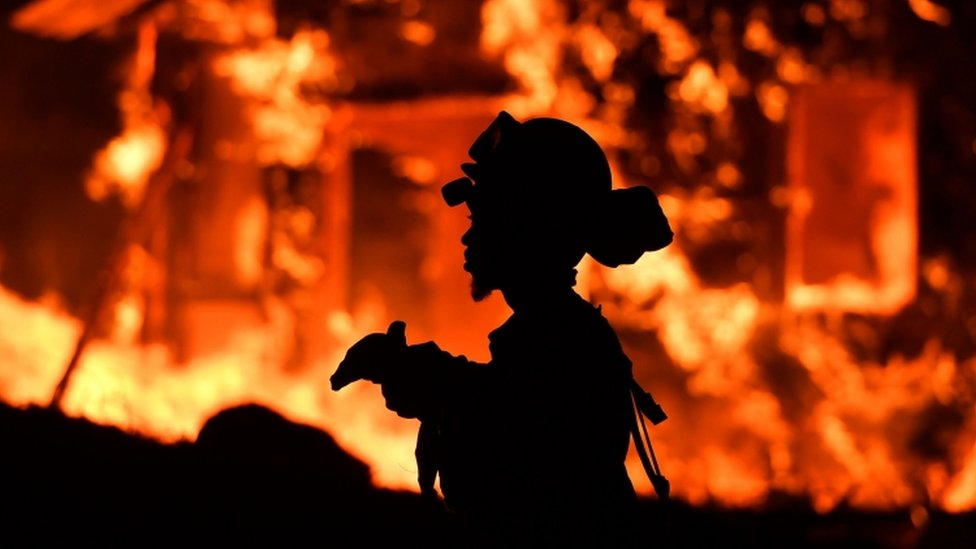 Silouette of firefighter with fire burning in background