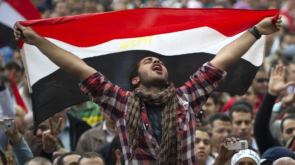 متظاهر يحمل علم مصر في ميدان التحرير بالقاهرة عام 2011