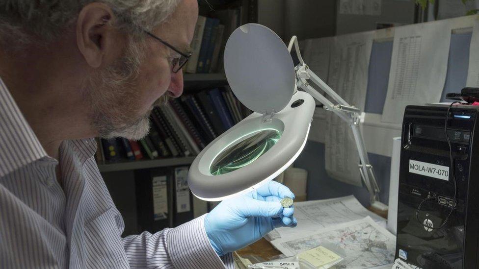 Julian Bowsher examina una moneda.