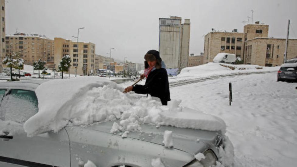 رجل يزيل الثلوج عن سيارته في العاصمة الأردنية عمان غداة عاصفة ثلجية ضربت البلاد