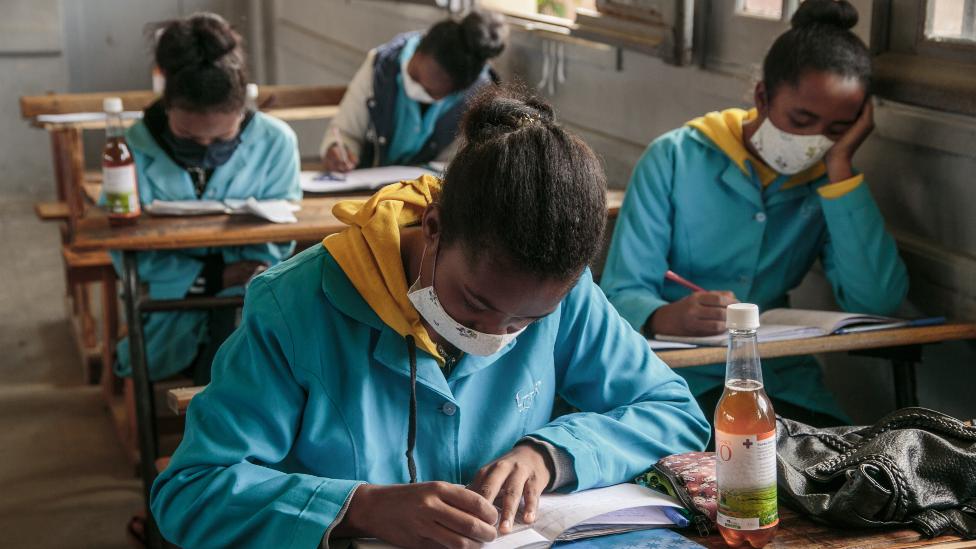 Anak sekolah di Madagaskar sedang belajar dan di meja mereka terdapat botol Covid-Organics April 2020