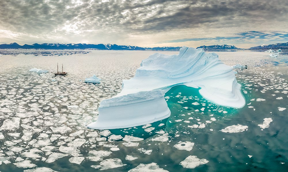 An expanse of icy water with an iceberg and a ship