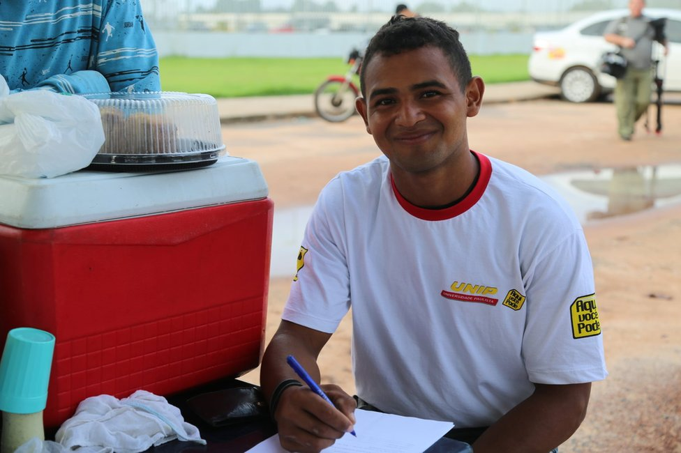 Jorge fills in a form outside the federal police station in Boa Vista