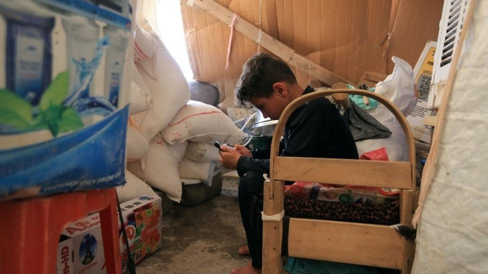 Grandson of displaced Yazidi Nayef al-Hamo plays with his mobile before leaving his home in Sharya town and heading back to Sinjar following the outbreak of the coronavirus and economic crisis, near Dohuk, Iraq July 3, 2020