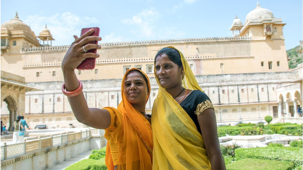 Women take a selfie in front of Amer fort and palace, India