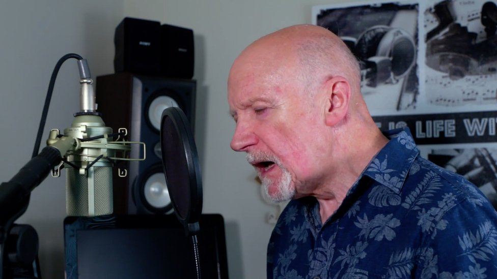Derick Davies singing on the microphone in his home music studio