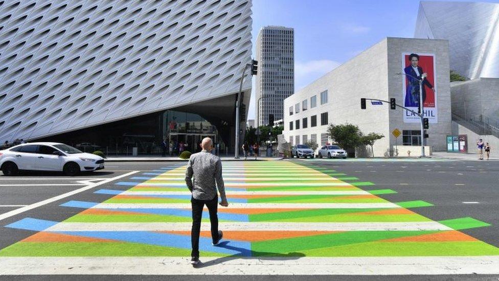 In this file photo taken on September 14, 2017 a man crosses a pedestrian crossing painted by Venezuelan artist Carlos Cruz-Diez toward the Broad Museum in Los Angeles, California.