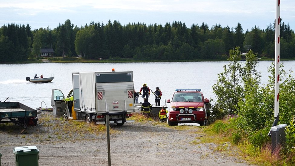 Emergency services arrive at a small harbour near the accident site at Ume river outside Umea, Sweden, on 14 July 2019