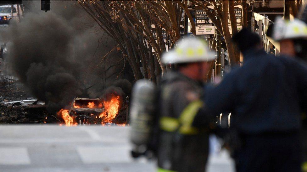 سيارة مشتعلة ورجال إطفاء بالقرب منها