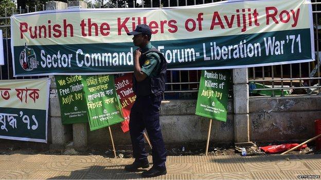 Police officer walks past banner calling for justice for Avijit Roy