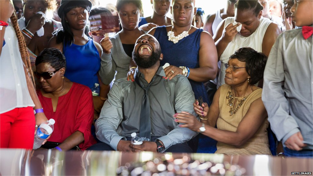 Michael Brown Sr. yells out as the casket is lowered into the ground during the funeral for his son Michael Brown at St. Peters Cemetery on August 25, 2014