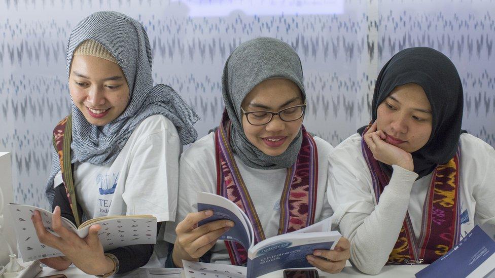 Tres chicas jóvenes leyendo