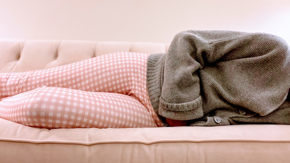 A photo of a woman lying on a sofa