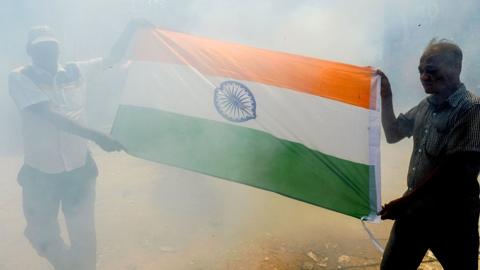 Indian residents hold the national flag through a cloud of smoke as they participate in a demonstration to support Indian armed forces in Chennai on February 26, 2019, following an Indian Air Force (IAF) strike launched on a Jaish-e-Mohammad (JeM) camp at Balakot.