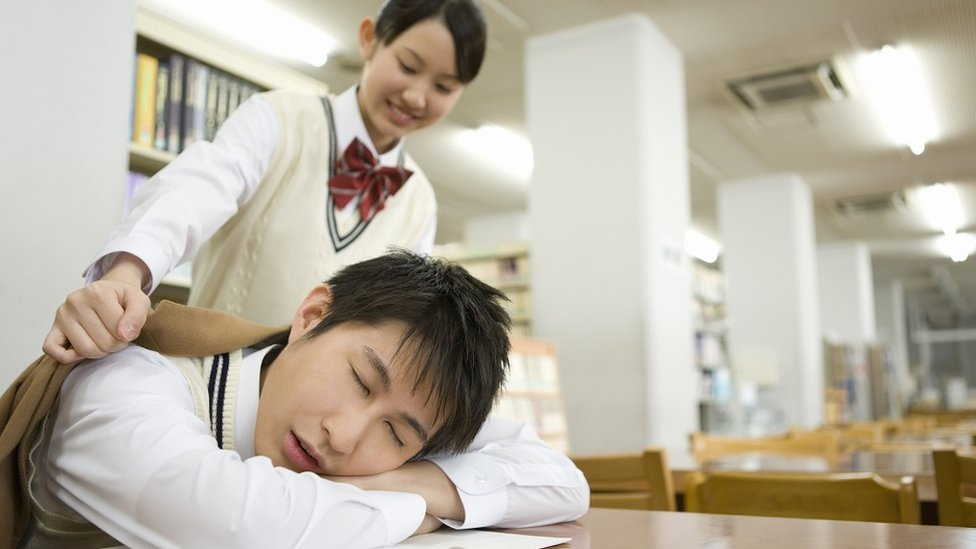 مراهق نائم - رأسه على الطاولة والكتب - في المكتبة؛ وفتاة عابرة تضع معطفا على كتفيه