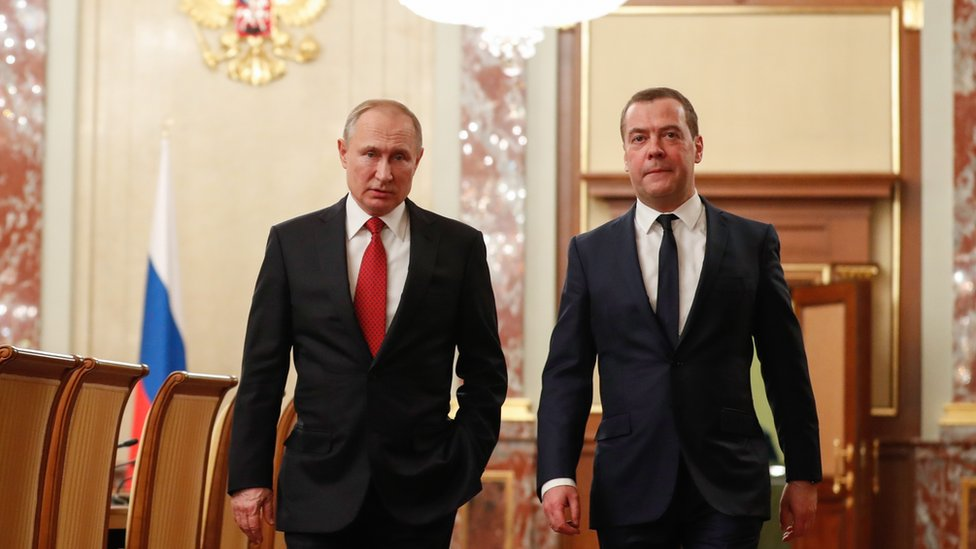 Russian President Vladimir Putin (L) and PM Dmitry Medvedev walking before a meeting with cabinet members