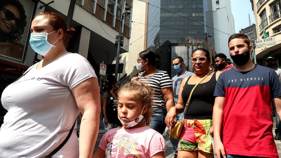 People shopping in São Paulo, walking next to each other without social distancing