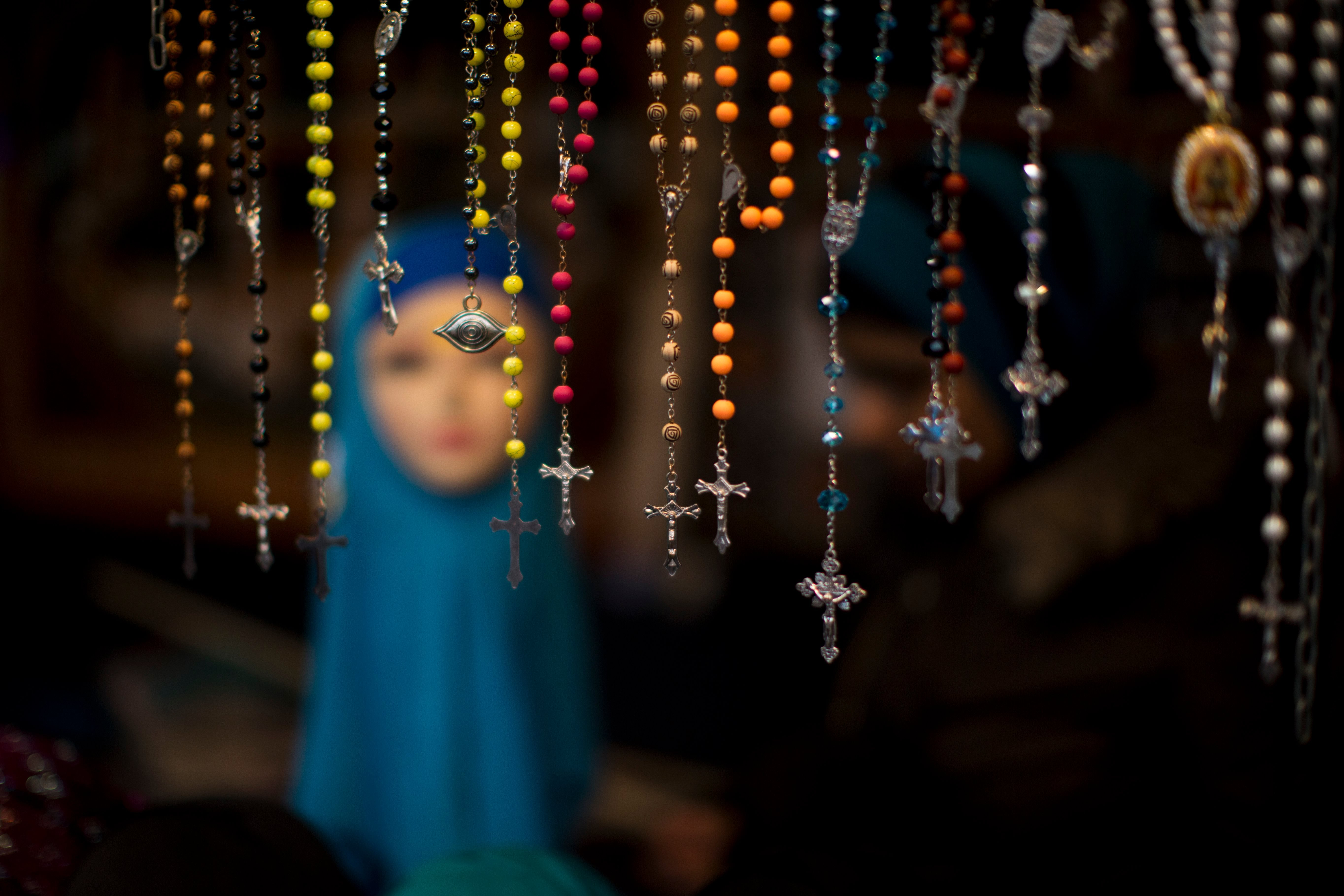 Rosary beads are displayed for selling next to a mannequin wearing a headscarf in a market stall at The Hague, The Netherlands.
