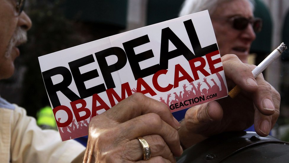"""A protester holds a """"repeal Obamacare"""" sign"""