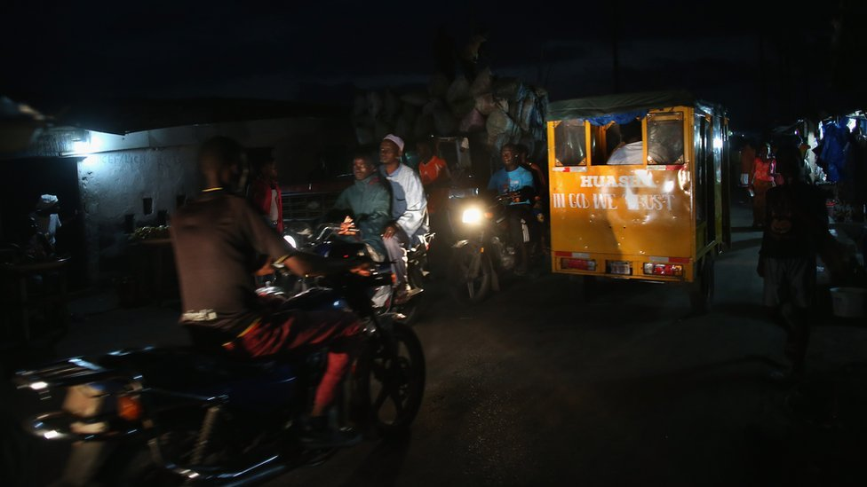 People drive through the dark in the West Point slum, where few homes have electricity, on August 15, 2014 in Monrovia, Liberia