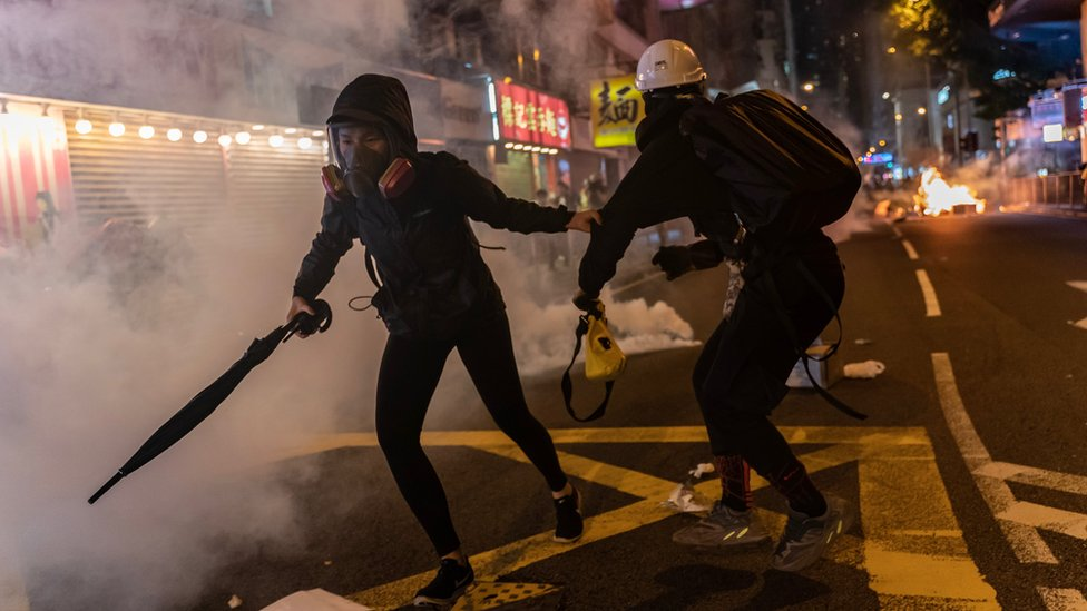 Pro-democracy protesters react as police fire teargas during a demonstration in Wan Chai district on November 2, 2019 in Hong Kong, China.