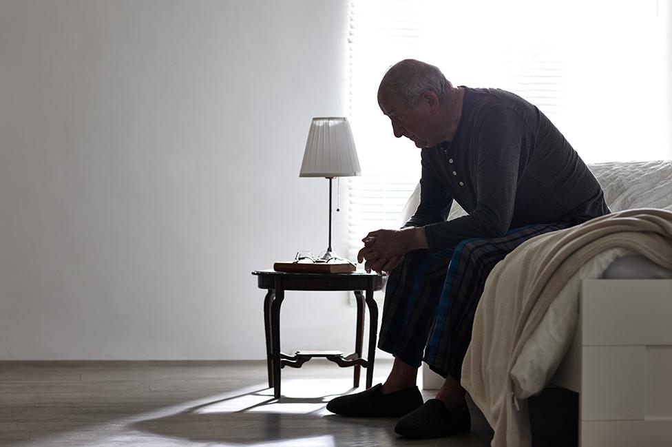 Un hombre mayor sentado en su cama