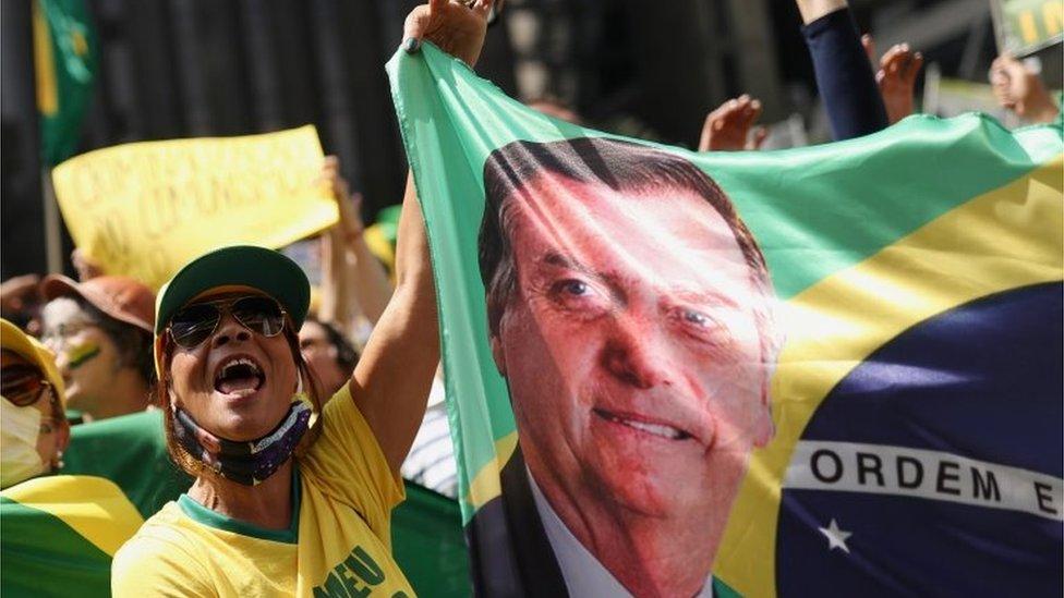 Apoiadora de Bolsonaro com bandeira do Brasil com rosto do presidente estampado